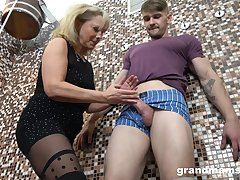 Old woman gives a blowjob and tugjob to young guy in a difficulty sauna